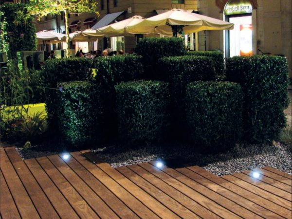 Exterior spotlights installed to wooden floor in a garden.